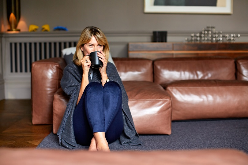 Shot of a mature woman sitting on her living room floor  drinking tea while wrapped in a blanket